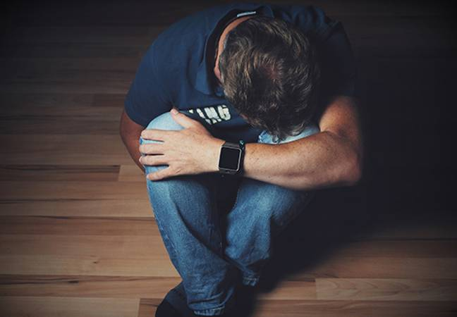 Depressed man with head in arms (Pixabay)